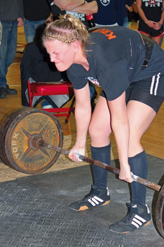 """With the face of focus and concentration, senior Crystal Krupp makes an effort to lift the bar at one of her matches. Krupp lifted for four years and has three state championships under her belt, but retired from the stress that lifing put on her body. She also got scholarship offers from colleges and even a chance to compete in the Olympics before """"retiring"""" from her powerlifting career."""