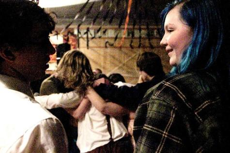 Two fans look to each other as the rest of the crowd huddles around a performer down off the stage.